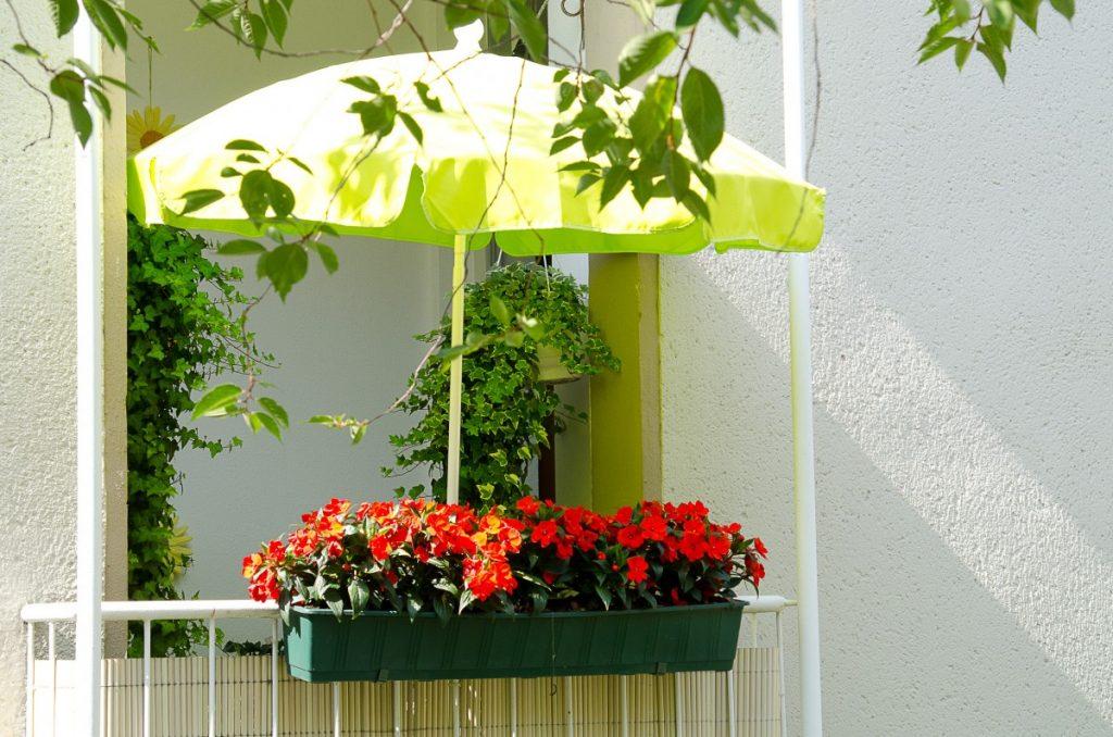 Kleiner Balkon mit Sonnenschirm und roten Blumen.