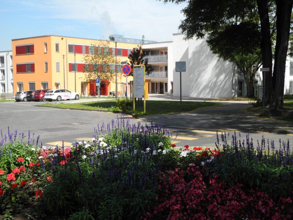 Modernes Pflegeheim mit Blumen im Vordergrund.