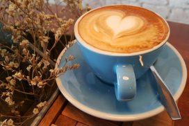 Blaue Tasse mit Kaffee auf einem Holztisch