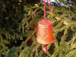 Rote Glocke mit Glitzer an einem Tannenzweig.