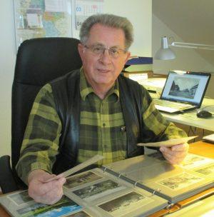 Herr Brokmeier an seinem Schreibtisch mit Alben voller historischer Ansichtskarten.