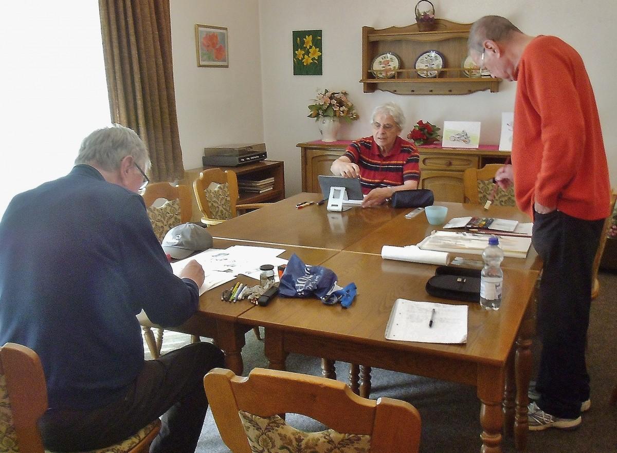 Drei Herren beim Malen an einem Tisch