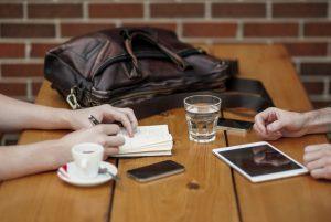 Zwei Nachbarn an ienem Tisch mit ihren Geräten
